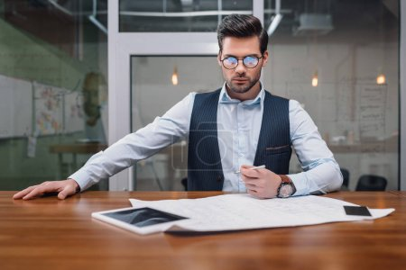 adult businessman in eyeglasses working with blueprint and gadgets in office