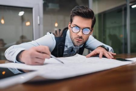 Photo pour Homme d'affaires adulte dans les lunettes de travail avec le plan dans le bureau - image libre de droit