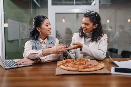 black and asian businesswomen eating pizza and working in office