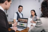 multiethnic business team with documents and laptop with shutterstock website
