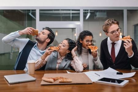 cheerful multiethnic businesspeople eating pizza in office