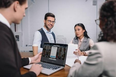 multiethnic business team with documents and laptop with linkedin website