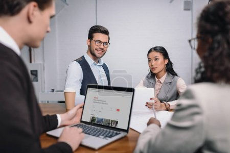 Photo for Multiethnic business team with documents and laptop with airbnb website - Royalty Free Image