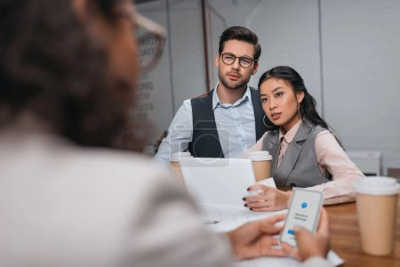 multiethnic businesspeople working together with tablet and smartphone with facebook messenger appliance