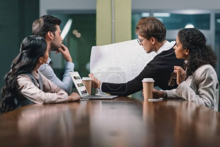 Photo for Multiethnic business team working with blueprint on meeting - Royalty Free Image