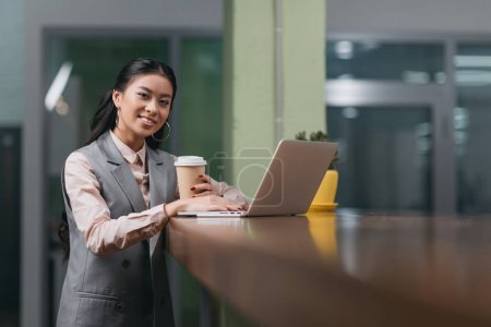 Photo for Young smiling asian businesswoman with coffee working with laptop in office - Royalty Free Image