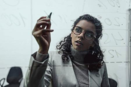 african american businesswoman working with glass board in office