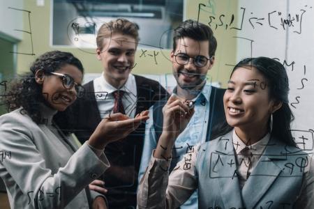 Photo pour Souriant multiethnique businesspeople écrit à bord de verre au bureau - image libre de droit