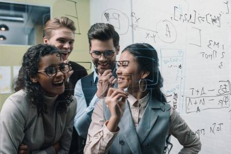 Photo for Smiling multiethnic businesspeople working with glass board in office - Royalty Free Image
