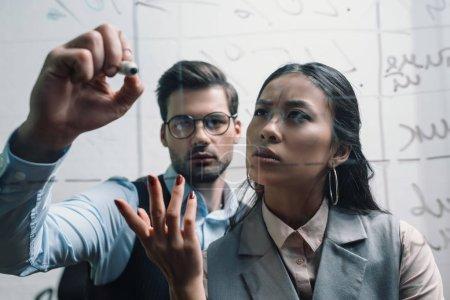 homme d'affaires et femme d'affaires asiatique, écrit à bord de verre au bureau