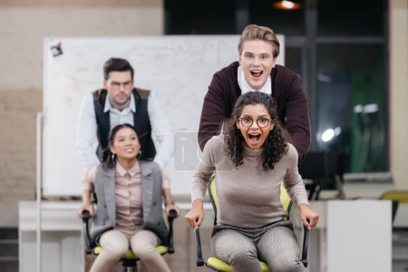 Photo for Happy multiethnic businesspeople have fun with swivel chairs in office - Royalty Free Image