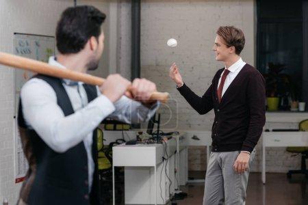 young businessmen playing baseball in officebaseball bat