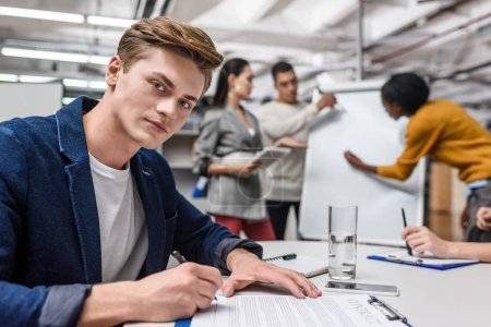 handsome young businessman signing contract while colleagues working on background