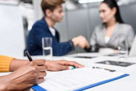 cropped shot of african american woman signing contract while blurred business partners shaking hands on background