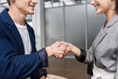 cropped shot of young business partners shaking hands