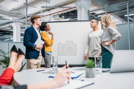 business partners standing in front of presentation board and having conversation