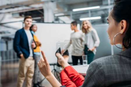 lady boss talking to workers in front of presentation board