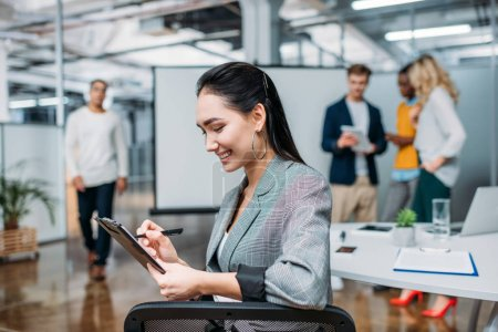 young beautiful businesswoman writing on clipboard at modern office with blurred colleagues on background