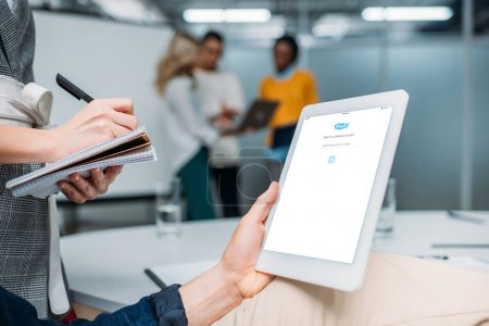 Photo for Businessman holding tablet with skype on screen at modern office while colleague making notes - Royalty Free Image