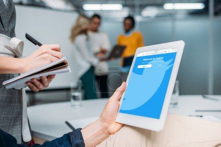 businessman holding tablet with twitter on screen at modern office while colleague making notes