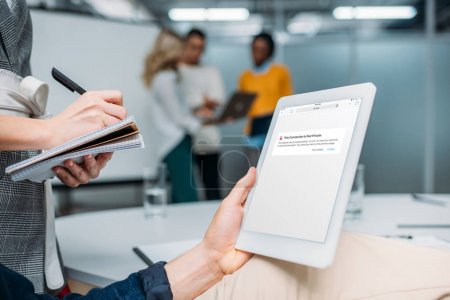 businessman holding tablet with browser app on screen at modern office while colleague making notes
