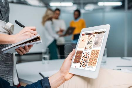 businessman holding tablet with pinterest on screen at modern office while colleague making notes