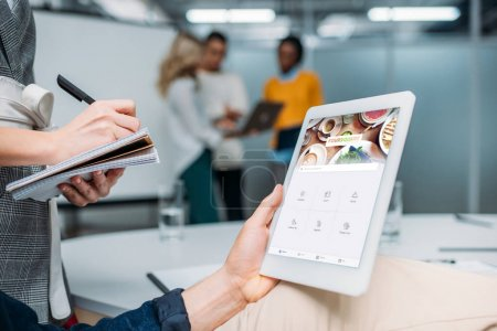 businessman holding tablet with forsquare app on screen at modern office while colleague making notes