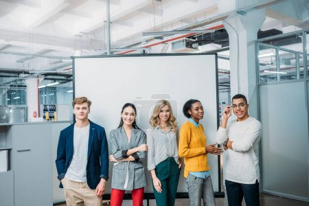 group of young business partners standing in front of whiteboard