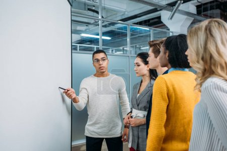 young handsome man making presentation for group of business partners