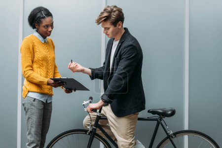 handsome young businessman signing contract in hands of young african american colleague while sitting on bike