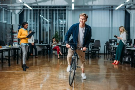 happy young businessman riding bike at modern office while his colleagues working