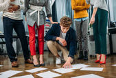 team of business partners standing over documents on floor