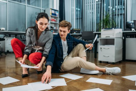 young business partners doing paperwork while sitting on floor at office