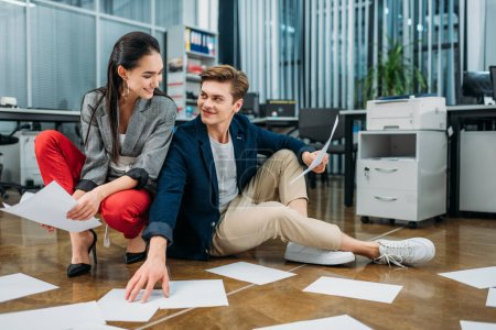 young happy business partners doing paperwork while sitting on floor at office