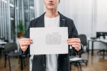 cropped shot of young man holding blank paper