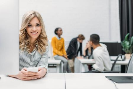 young beautiful woman using smartphone at office