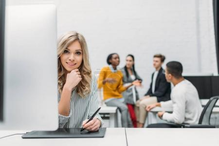 young designer drawing with tablet with blurred partners on background