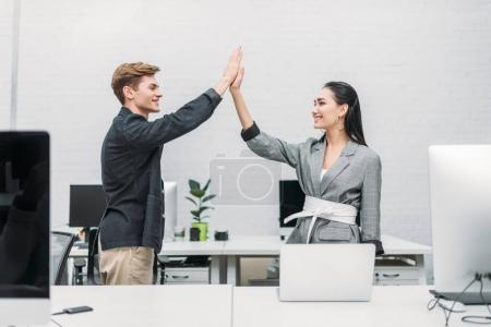 multiethnic business partners giving high five at office