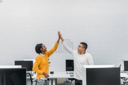 Photo pour Jeune entreprise afro-américain partenaires donnant cinq haut au bureau - image libre de droit