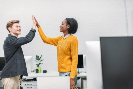 happy young business partners giving high five in modern office