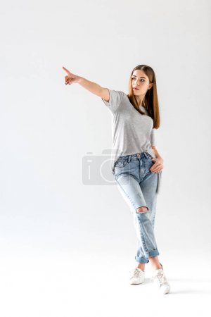 attractive young woman pointing and looking away,  isolated on white