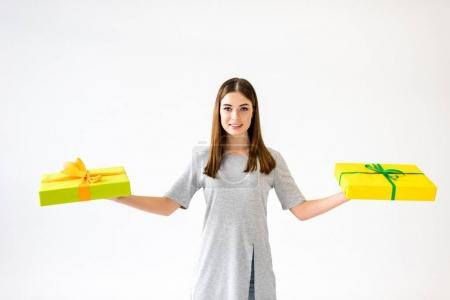 portrait of smiling young woman holding presents in hands,  isolated on white