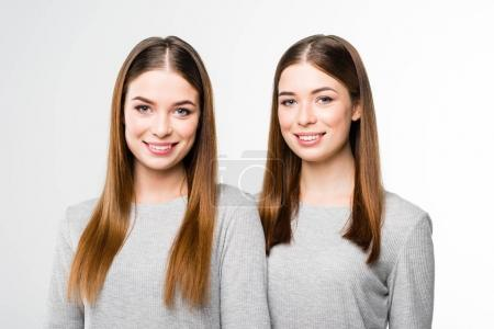 portrait of young smiling twins in grey tshirts looking at camera