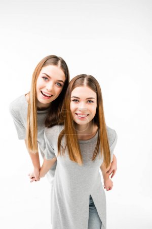 portrait of happy twins in grey tshirts holding hands and looking at camera isolated on white