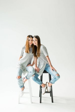 young cheerful twins in similar clothing looking at camera while sitting on chairs