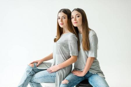 Photo for Young twins in similar clothing looking at camera while sitting on chairs - Royalty Free Image