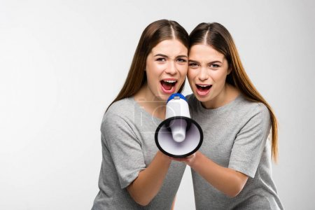 portrait of young twins screaming into loudspeaker in hands
