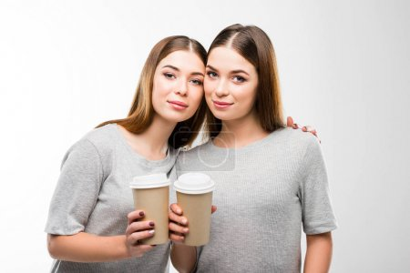 portrait of beautiful twins with coffee to go in hands looking at camera