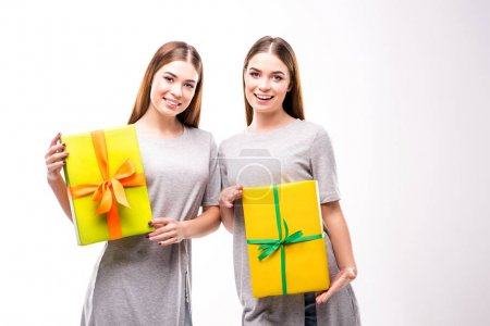 portrait of cheerful twins holding wrapped gifts in hands