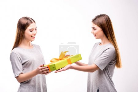 side view of smiling woman presenting wrapped gift to twin sister